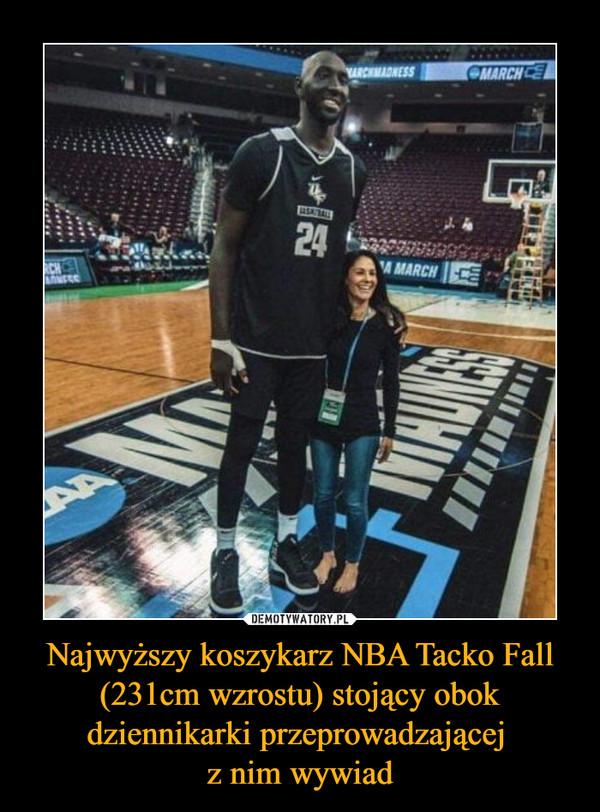 Najwyższy koszykarz NBA Tacko Fall (231cm wzrostu) stojący obok dziennikarki przeprowadzającej z nim wywiad –